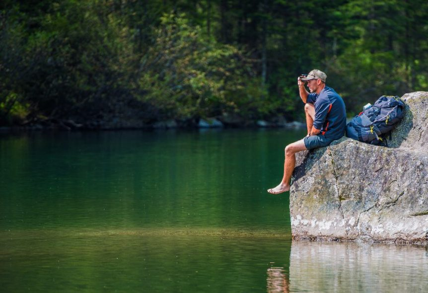 man sitting on rock by lake